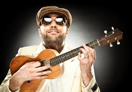 ukelele: funny man with glasses play guitar ukelele on black background