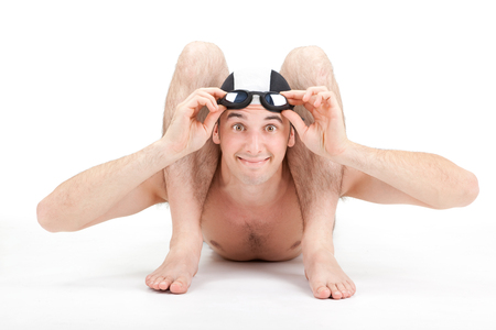 contortion: smiling happy flexible contorsionist swimmer with cap and goggles on grey background