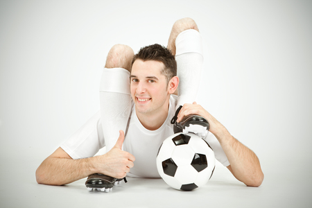 contortion: Contorsionist flexible soccer football player thumb up ball under foot on grey background