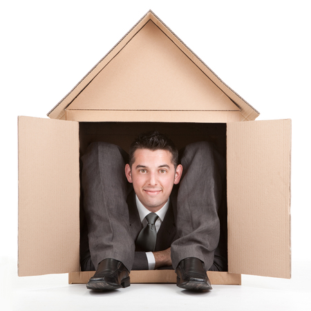 contortion: elegant smiling happy flexible contortion businessman in cardboard house