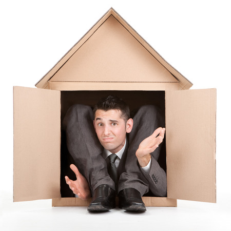 contortion: elegant disappointed flexible contortion businessman in cardboard house Stock Photo