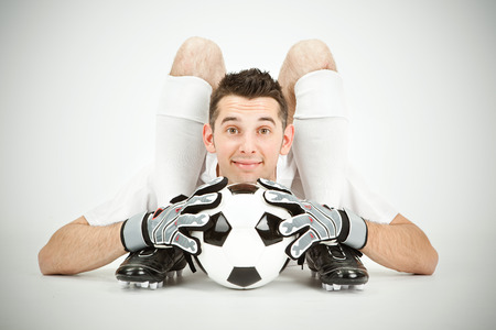 contortion: Contorsionist flexible soccer football player goalkeeper with ball on grey background
