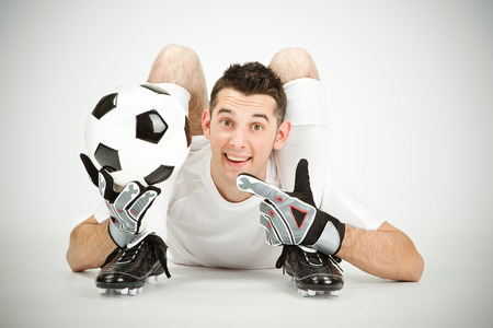contortion: Contorsionist flexible soccer football goalkeeper player show ball on grey background Stock Photo