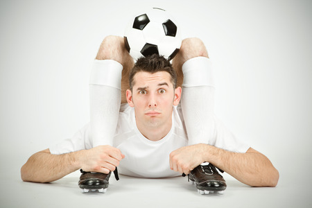 contortion: Contorsionist surprised flexible soccer football player with ball on head on grey background Stock Photo