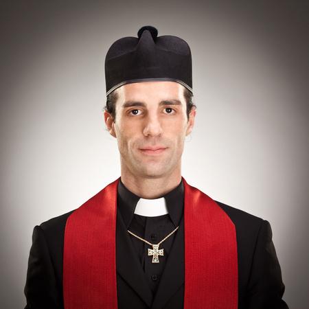 spiritualism: young cristian catholic priest with crucifix smile portrait on grey background Stock Photo