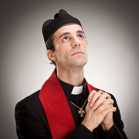 clergyman: young cristian catholic priest with crucifix pray portrait on grey background