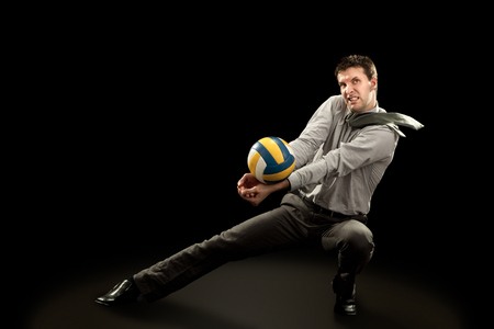 fun at work: sport businessman plays volleyball on black background Stock Photo