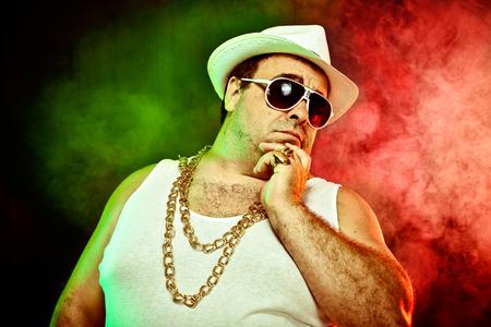 rapero: italiano divertido rapero jefe de la mafia con la camiseta y gafas de sol sobre fondo ahumado Foto de archivo