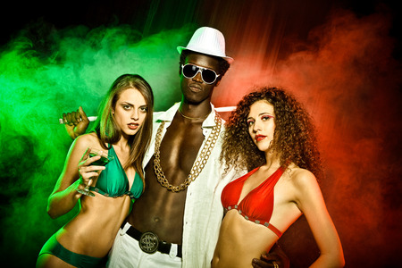 rapper: Black young rapper with two girls in bikini red green at club Stock Photo