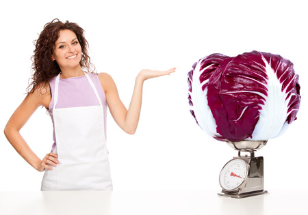 radicchio: Beautiful young housewife scale a huge radicchio isolated on white