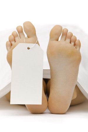 toe tag: dead body feet with card autopsy isolated on white Stock Photo
