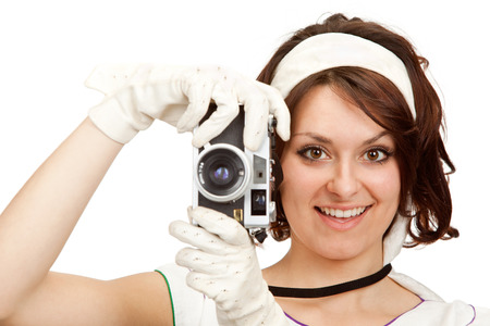 80s adult: beautiful vintage girl take photograph with old camera isolated on white