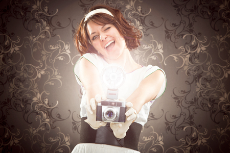 70s adult: beautiful vintage girl take photograph with old camera on tapestry background