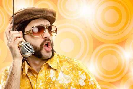 hawaiian shirt: 1970s vintage show man sing with hawaiian shirt and microphone on yellow background