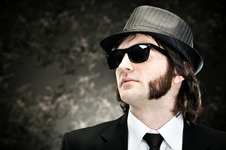 sideburns: elegant boss man with sideburns and sunglasses on black backround