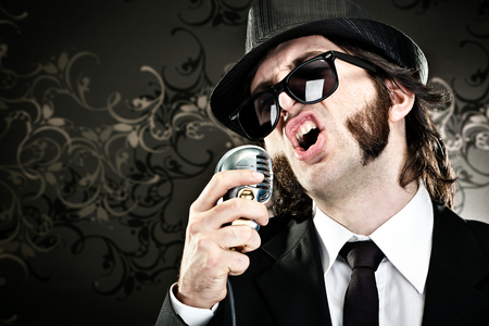 sideburns: elegant boss man with sunglasses and microphone singing portrait on black background