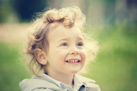 curly hair child: beautiful blond curly hair child play outdoor in a park