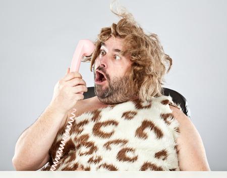 prehistoric man: ugly rude prehistoric man talking on the phone Stock Photo