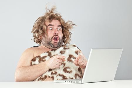hombre prehistorico: el hombre prehistórico divertida sorprendida usando la computadora portátil Foto de archivo