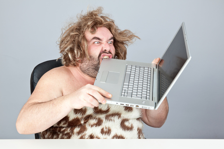 hungry and angry prehistoric man eat laptop
