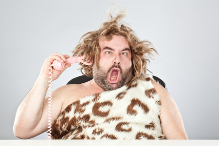 ugly rude prehistoric man with phone in his hair