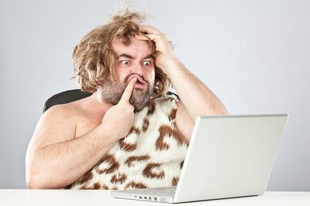 brutto uomo preistorico dubbioso sul computer portatile