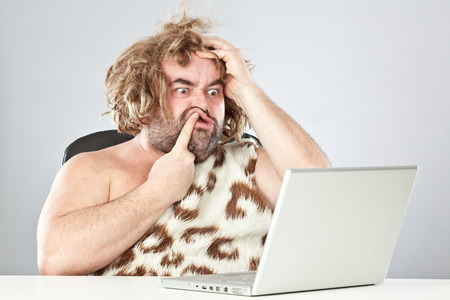 ugly doubtful prehistoric man on laptop
