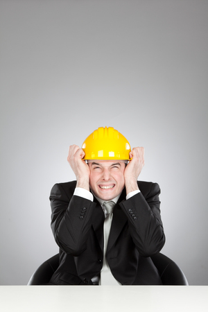 deafening: young deafened engineer with yellow helmet and laptop isolated on grey