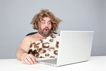 hombre prehistorico: el hombre prehistórico perplex divertida usando la computadora portátil