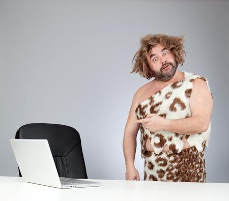 funny perplex prehistoric man using laptop