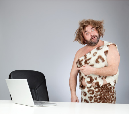 funny perplex prehistoric man using laptop