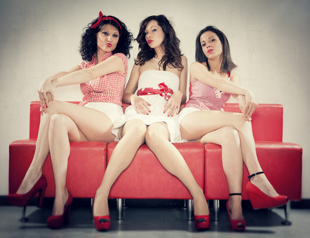 red sofa: three pin-up girl sit on a red sofa Stock Photo
