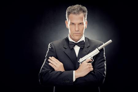 蝶ネクタイと黒に分離された銃を持つエレガントな男