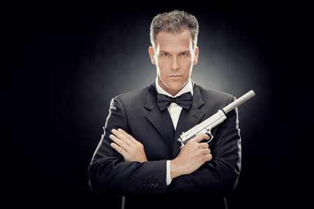 elegant man with bow tie and gun isolated on black Banco de Imagens