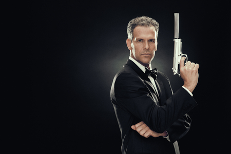 elegant man with bow tie and gun isolated on black Stock Photo