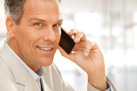 telephone salesman: handsome smiling businessman talk on phone at office Stock Photo