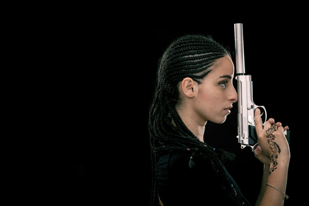 dread: Beautiful dread young woman with gun portrait isolated on black Stock Photo