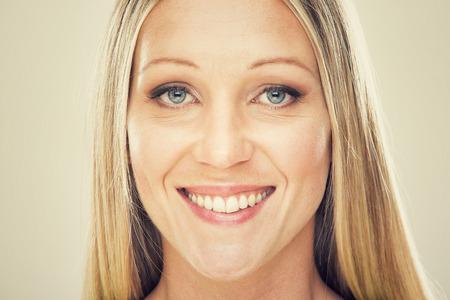 dientes sanos: hermosa mujer rubia sonriente aislado en gris Foto de archivo
