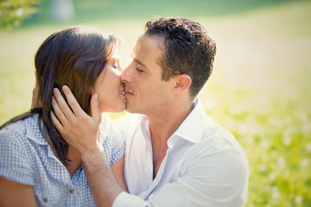 couple kiss: young brunette couple kiss together at the park