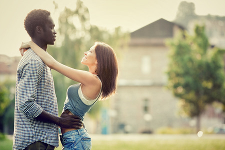 couple laughing: young multi-ethnic couple having fun together at the park