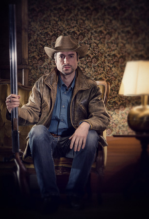 gaze: handsome cowboy with sensual gaze and rifle  in a old house Stock Photo