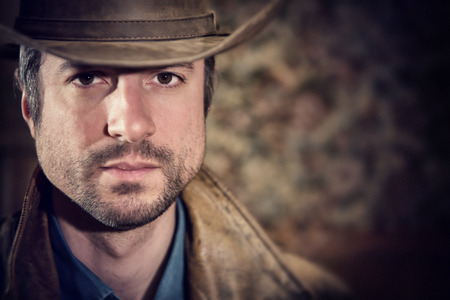 gaze: handsome cowboy with sensual gaze and hat in a old house