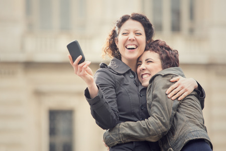 black lesbian: couple of smiling women take selfie in cityscape