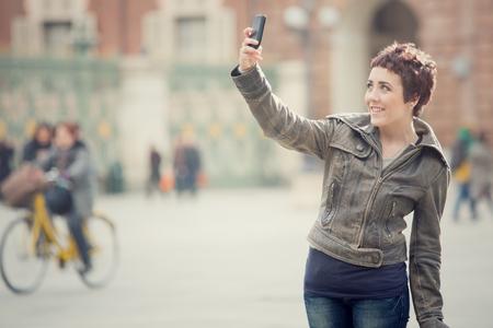 cabello corto: mujer sonriente pelo corto tomar autofoto en el paisaje urbano Foto de archivo