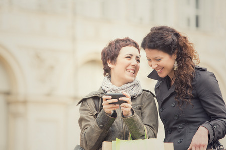 couple of women shop together with phone in cityscape