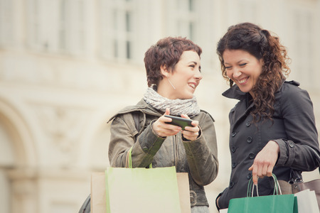 black lesbian: couple of women shop together with phone in cityscape