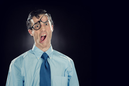 funny glasses: nerd businessman with glasses make funny face isolated on black