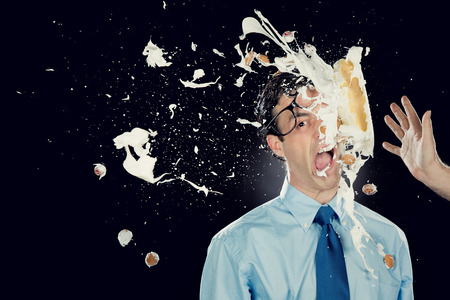 nerd businessman with cake on face isolated on black
