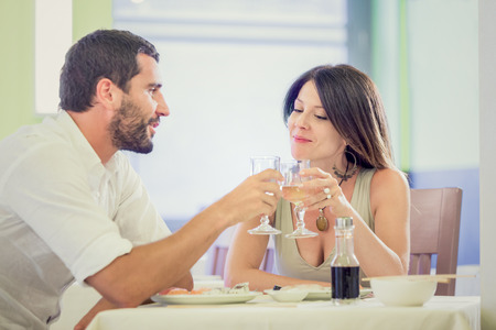 each: Young romantic couple drink to each other at restaurant Stock Photo