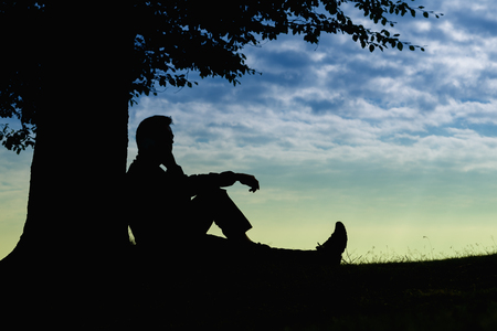 Man silhouette sitting under tree with phone on cloudy day outdoor